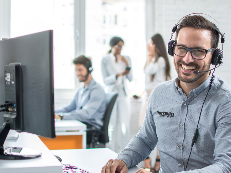 Customer Service Representative Smiling, Sitting At A Computer
